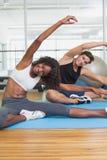 Couples convenables réchauffant sur des tapis d'exercice Photos stock