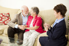Couples Counseling - Happy Outcome. Therapist looks on as a senior couple she's been counseling works out their issues Royalty Free Stock Photography