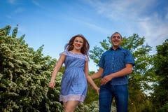 Couples courant au printemps le parc de floraison Jeune homme et femme ayant l'amusement au coucher du soleil Photo stock