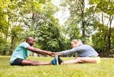 Couples courants s'étendant et réchauffant en parc avant la formation Images stock