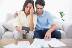 Couples craintifs faisant leurs comptes Image stock