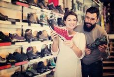 Couples décidant de nouvelles espadrilles Photographie stock libre de droits