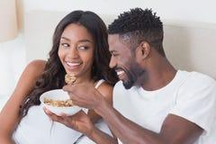 Couples décontractés dans le lit mangeant ensemble de la céréale Photographie stock