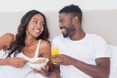 Couples décontractés dans le lit mangeant ensemble de la céréale Photos libres de droits
