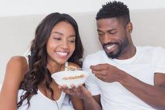 Couples décontractés dans le lit mangeant ensemble de la céréale Images libres de droits