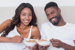 Couples décontractés dans le lit mangeant ensemble de la céréale Photo stock