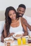 Couples décontractés prenant le petit déjeuner dans le lit ensemble Images stock