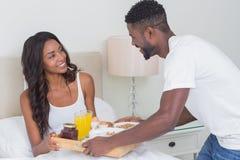 Couples décontractés prenant le petit déjeuner dans le lit ensemble Photos libres de droits
