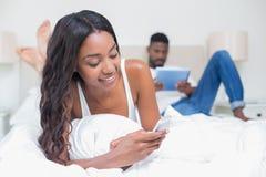 Couples décontractés utilisant la technologie sur le lit Images stock