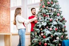 Couples décorant l'arbre de nouvelle année à l'intérieur image stock