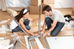 Couples déménageant dans la table se réunissante ensemble de meubles Photo libre de droits