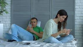 Couples dépendants aux smartphones et aux jeux en ligne banque de vidéos