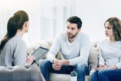 Couples déprimés gentils regardant leur thérapeute Image stock
