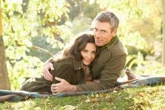 Couples détendant à l'extérieur dans l'horizontal d'automne Photographie stock libre de droits