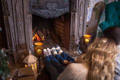 Couples détendant à la maison le cacao potable Les pieds en laine cogne près de la cheminée Concept de vacances d'hiver Photos libres de droits