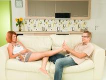 Couples détendant à la maison sur le sofa Photo stock