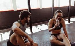 Couples détendant après session de séance d'entraînement au gymnase Images libres de droits
