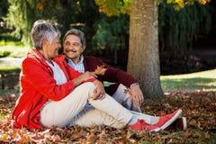 Couples détendant au parc pendant l'automne Photographie stock