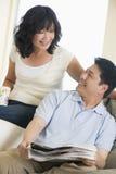 Couples détendant avec un journal et un sourire Photographie stock