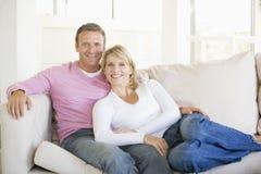 Couples détendant dans la salle de séjour et le sourire Photos stock