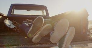Couples détendant dans le camion pick-up à la plage 4k banque de vidéos