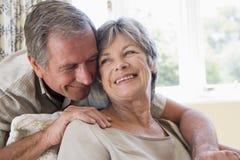 Couples détendant dans le sourire de salle de séjour Photo libre de droits