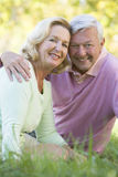 Couples détendant dans le sourire de stationnement Photographie stock libre de droits