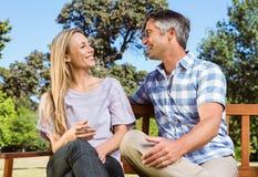 Couples détendant en parc sur le banc Image libre de droits