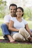 Couples détendant en stationnement Photographie stock libre de droits