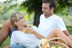 Couples détendant sur l'herbe Photographie stock libre de droits