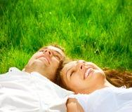 Couples détendant sur l'herbe verte Image libre de droits