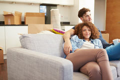 Couples détendant sur la nouvelle maison de Sofa With Hot Drink In Photographie stock libre de droits
