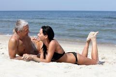 Couples détendant sur la plage Photos libres de droits