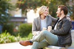 Couples détendant sur le banc de parc avec du café à emporter photo libre de droits