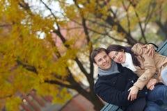 Couples détendant sur le banc de stationnement Images stock