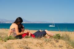 Couples détendant sur le sable Photo stock