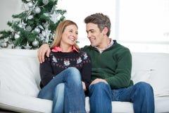 Couples détendant sur Sofa During Christmas images stock