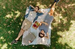 Couples détendant sur un pique-nique au parc Photos stock