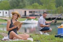 Couples détendant tout en pêchant au lac Photos stock