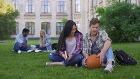 Couples d'étudiant se reposant sur l'herbe près de l'université, parlant et souriant, première passion banque de vidéos