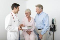 Couples d'aîné de docteur Showing Reports To Photo stock