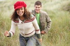 Couples d'adolescent marchant par des dunes de sable Images stock