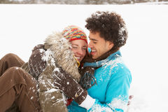 Couples d'adolescent romantiques ayant l'amusement dans la neige Photographie stock