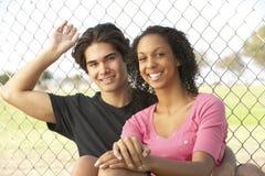 Couples d'adolescent se reposant dans la cour de jeu Images libres de droits