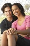 Couples d'adolescent se reposant dans la cour de jeu Images stock