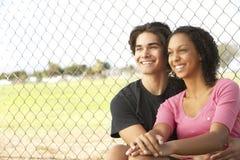 Couples d'adolescent se reposant dans la cour de jeu Image libre de droits