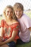 Couples d'adolescent se reposant dans la cour de jeu Photo stock