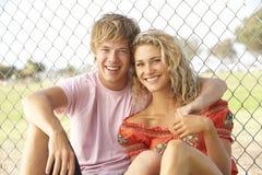 Couples d'adolescent se reposant dans la cour de jeu Photos stock
