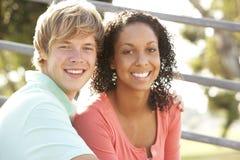 Couples d'adolescent se reposant dans la cour de jeu Image stock