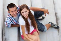Couples d'adolescent se reposant sur des escaliers Photo stock